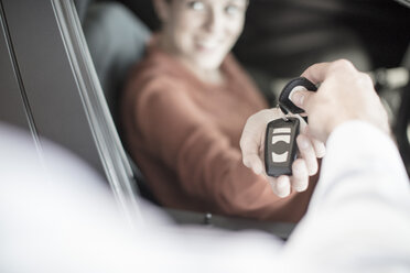 Car dealer handing over key to woman at car dealership - ZEF11569