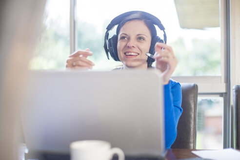 Smiling woman at desk with laptop and headset - ZEF11581