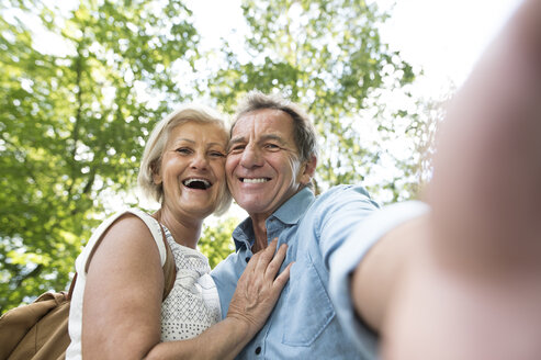 Happy senior couple taking selfie in the woods - HAPF01072