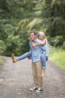 Senior man giving his wife a piggyback ride on forest track - HAPF01075