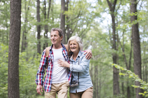 Happy senior couple walking arm in arm in the woods - HAPF01081