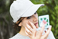 Woman using pocket mirror for checking her make up - GIOF01597