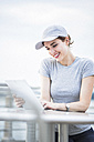 Smiling woman with basecap looking at tablet - GIOF01603