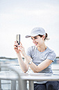 Smiling woman with basecap taking selfie with cell phone - GIOF01606