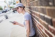 Woman with smartphone leaning against brick wall - GIOF01621