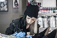 Female tattoo artist tattooing a leg - ZEF11591