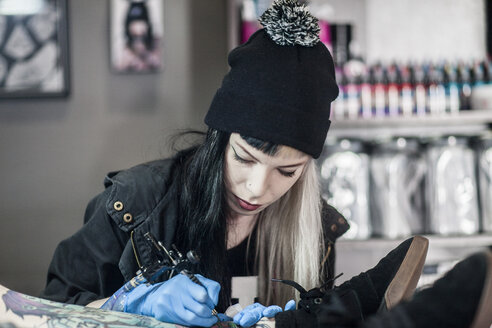 Female tattoo artist tattooing a leg - ZEF11591