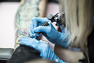 Female tattoo artist tattooing a leg - ZEF11594