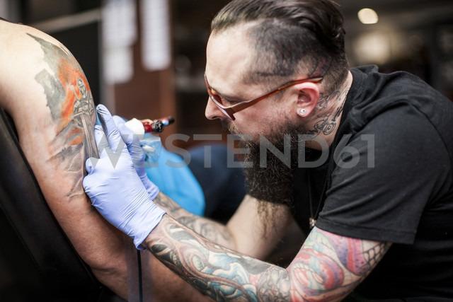 Tattoo artist tattooing an arm - ZEF11600