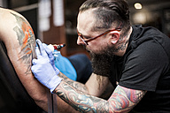 Tattoo artist tattooing an arm - ZEF11600