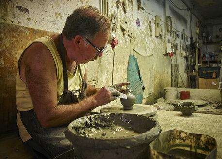 Potter in workshop working on earthenware vessel - DIKF00241