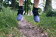 Shoes of jogger jumping on forest track - BOYF00636