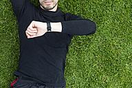 Jogger lying in grass looking on watch - BOYF00642