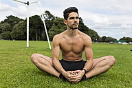 Barechested athlete sitting in grass - BOYF00657