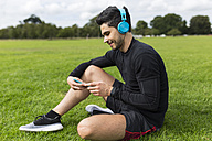 Athlete sitting in grass listening to music - BOYF00663