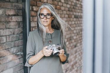 Woman with long grey hair holding camera - KNSF00447