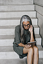 Woman with long grey hair sitting on stairs holding tablet - KNSF00462