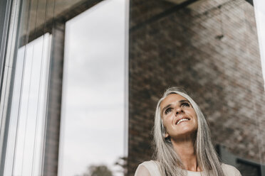 Smiling woman with long grey hair looking out of window - KNSF00474
