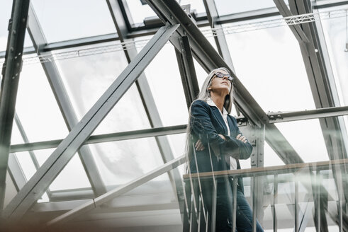 Woman with long grey hair standing in a loft - KNSF00486