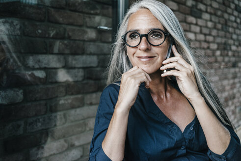 Smiling woman with long grey hair on cell phone - KNSF00495