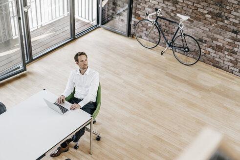 Businessman using laptop in office - KNSF00504
