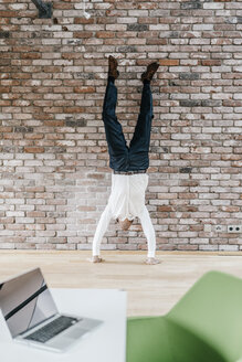 Businessman doing a handstand in front of brick wall - KNSF00522