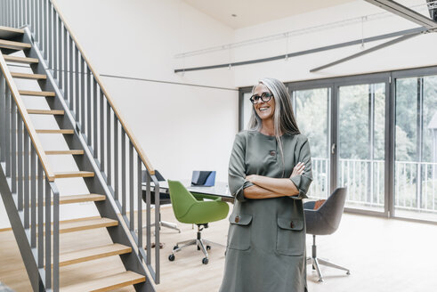 Smiling woman with long grey hair in office - KNSF00540