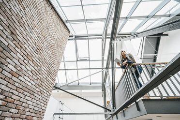 Woman with long grey hair standing in a loft - KNSF00558