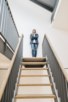 Confident businesswoman with long grey hair standing on top of stairs - KNSF00561
