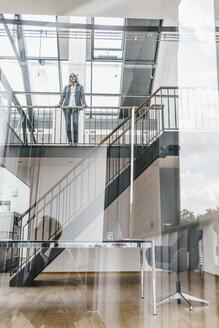 Businesswoman in a loft with reflexion of businessman - KNSF00570