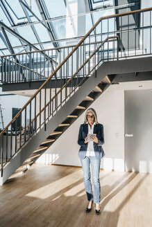 Businesswoman with long grey hair using tablet in a loft - KNSF00576