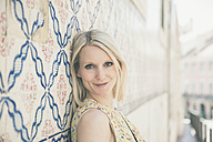 Portugal, Lisbon, portrait of smiling blond woman leaning against wall with Azulejos - CHPF00310