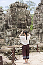 Cambodia, Siem Reap, Angkor Thom, back view of tourist taking pictures of Bayon temple - MADF01216