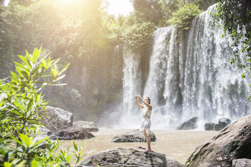 Cambodia, Nationalpark Phnom Kulen, young woman taking selfie with smartphone in front of waterfalls - MADF01225