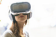 Woman wearing Virtual Reality Glasses and headphones - TAMF00770