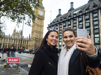 UK, London, two happy friends taking selfie with smartphone in front of Big Ben - AMF05055
