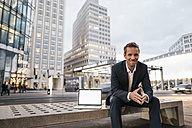 Germany, Berlin, Potsdamer Platz, portrait of businessman sitting on bench with laptop - KNSF00650