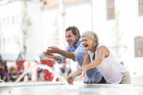 Senior couple siplashing with water of a fountain - HAPF01121
