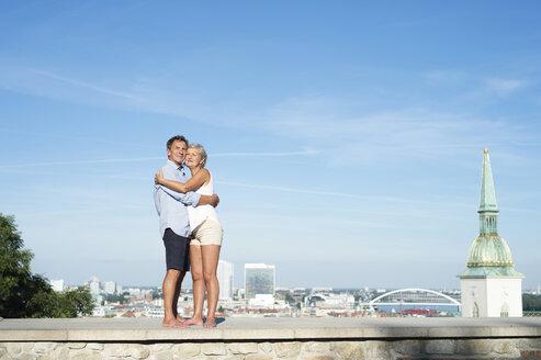Slovakia, Bratislava, happy couple standing on a wall hugging - HAPF01148