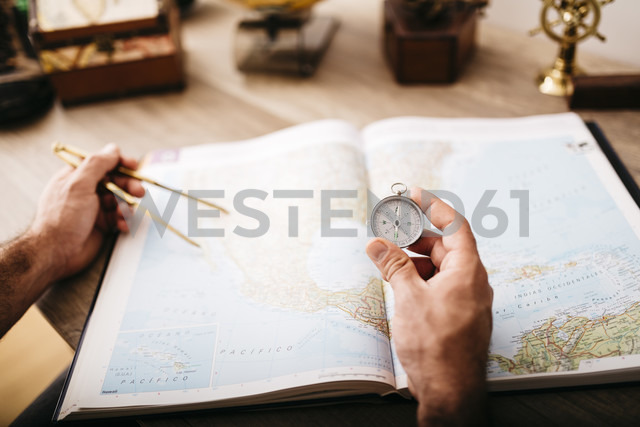 Young man planning journey using compasses - JRF01025