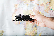 Man holding toy locomotive in front of word map - JRFF01028