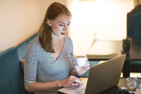 Portrait of woman sitting in a coffee shop using laptop - TAMF00786
