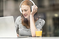 Portrait of smiling woman sitting in a coffee shop using headphones and laptop - TAMF00789