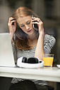 Portrait of pensive woman on the phone sitting in a coffee shop - TAMF00792
