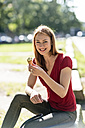 Portrait of smiling woman eating icecream - TAMF00801