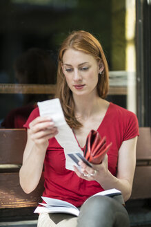 Portrait of woman checking sales slip - TAMF00804