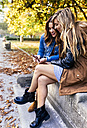 Two young women with smartphone in a park in autumn - MGOF02592