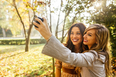 Two smiling young women taking a selfie in a park in autumn - MGOF02598