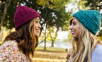 Two smiling young women wearing wooly hats in a park in autumn - MGOF02601