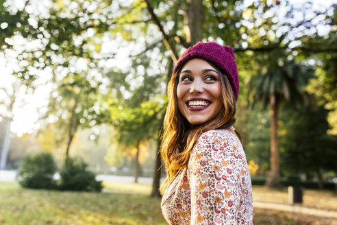 Happy young woman wearing wooly hat in a park in autumn - MGOF02604